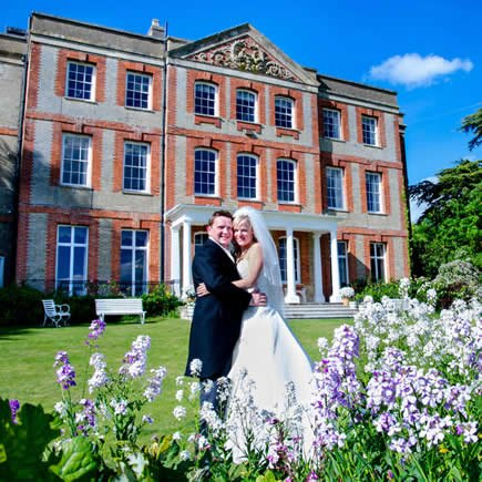 Bride and groom with wildflowers at their wedding in front of Ardington House - Mark Sisley Photography