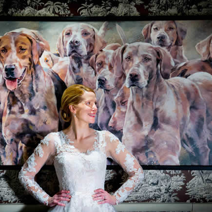 Bride in front of painting of beagles at her wedding at the Bay Tree Hotel Cotswolds UK - Mark Sisley Photography