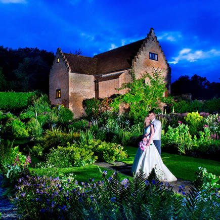 Bride and groom at twilight in front of Chenies Manor - Mark Sisley Photography