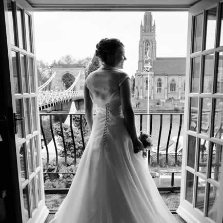 Black and white bride looking through window at Compleat Angler Marlow Bucks - Mark Sisley Photography