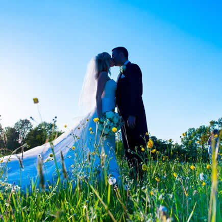 Bride and groom in wildflowers - Mark Sisley Photography