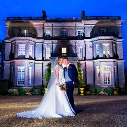 Dramatically lit image of bride and groom at twilight in front of Hedsor House Buckinghamshire - Mark Sisley Photography