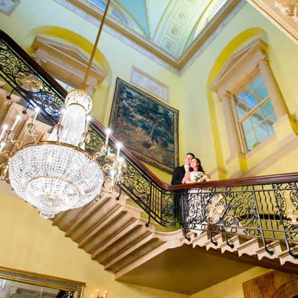 Bride and groom on staircase at Stoke Park Buckinghamshire - Mark Sisley Photography