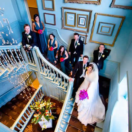 Bridal party on staircase at Stoke Place Buckinghamshire - Mark Sisley Photography