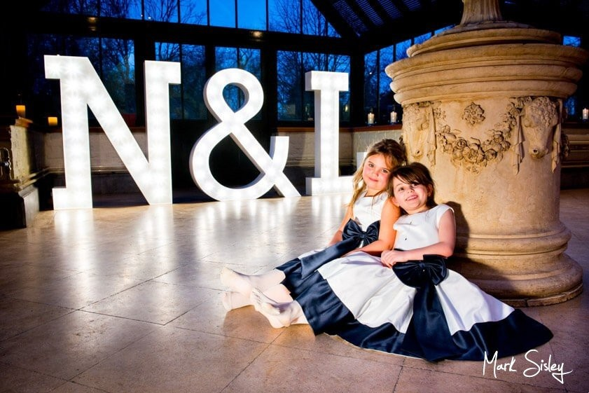 Young bridesmaids in front of giant letters - wedding at The Dairy Waddesdon Manor - Mark Sisley Photography