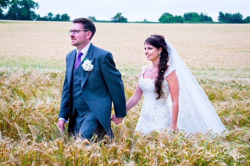 Bride and Groom walking through wheat field - wedding at Clearwell Castle - Mark Sisley Photography