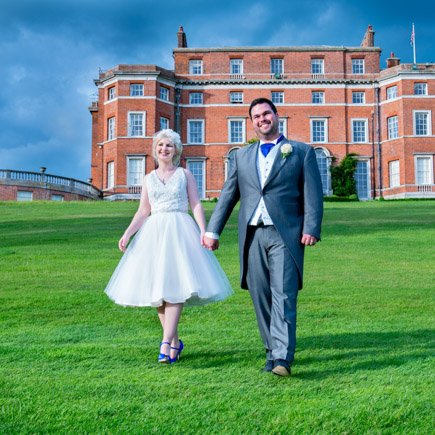 Bride and groom walking on the lawn in front of Brocket Hall Hertfordshire - wedding at Brocket Hall
