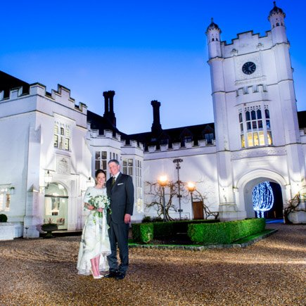 Bride and groom in front of Danesfield House at twilight