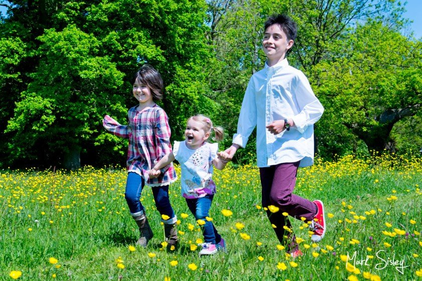 children running in a meadow - family portrait photograph - Mark Sisley Photography