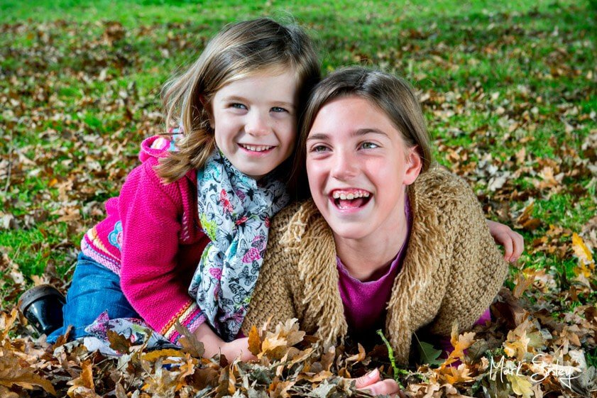 young girls laughing in autumn leaves - family portrait photograph - Mark Sisley Photography