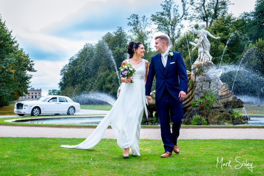 Bride and groom walking on the lawn - wedding at Cliveden House - Mark Sisley Photography