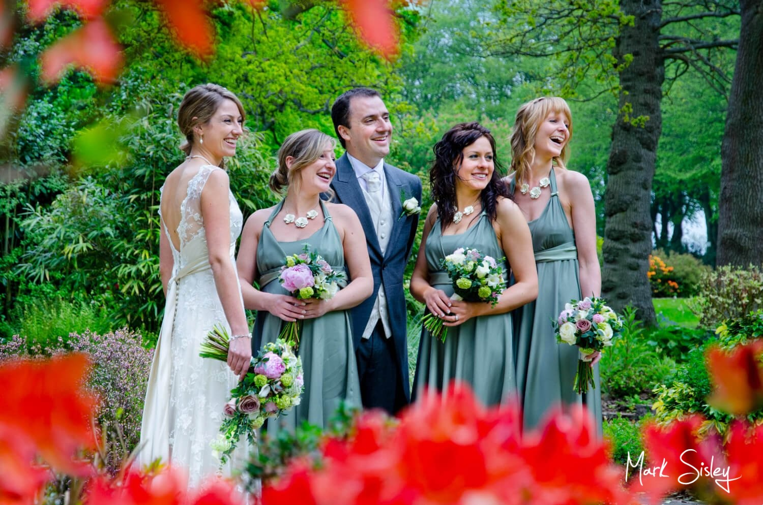 Bride and groom and bridesmaids in mint green dresses with rhododendrons in the foreground at Chartridge Lodge by Mark Sisley Photography