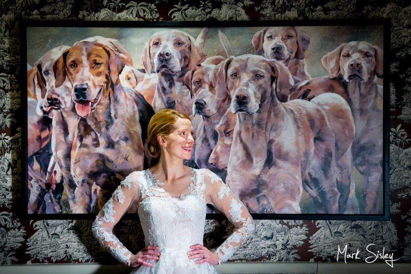 Bride posed in front of painting of dogs - Mark Sisley Photography