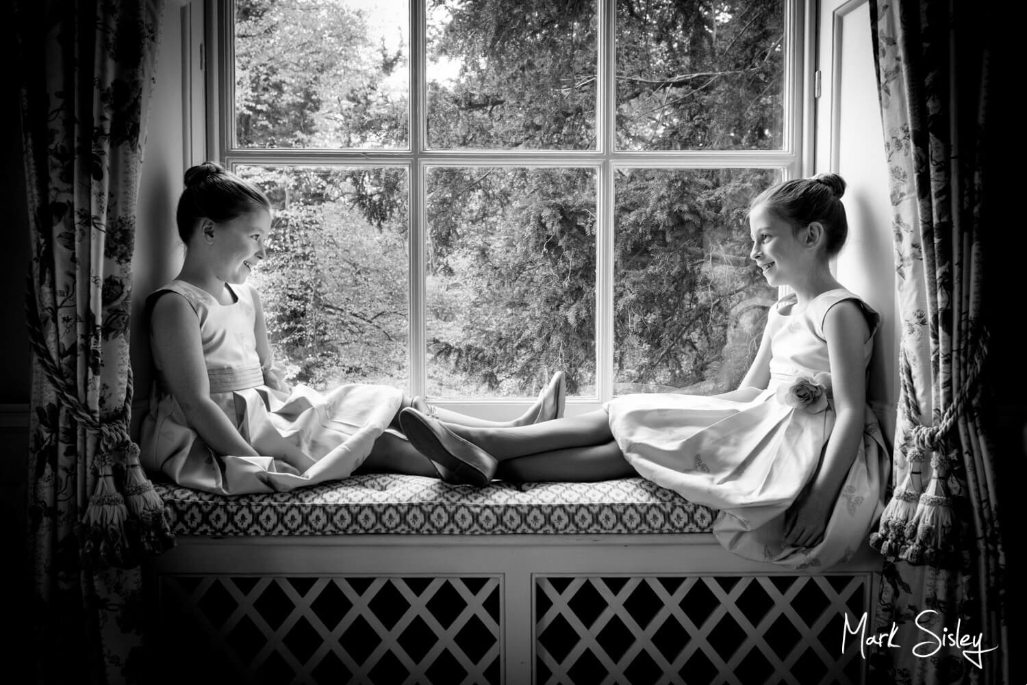 Beautiful black and white image of two young bridesmaids on the window ledge at a wedding at Hartwell House Hotel Bucks by Mark Sisley Photography