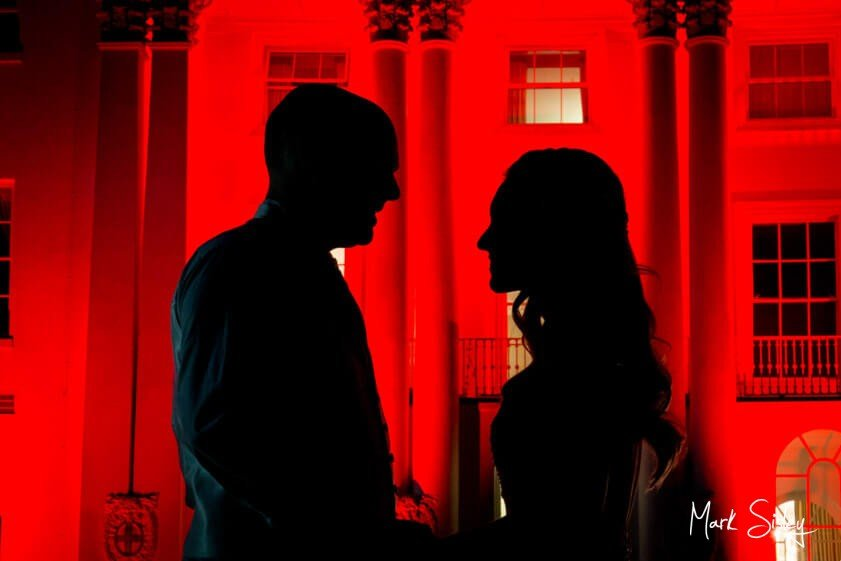 Couple in silhouette against red backdrop - Mark Sisley Photography