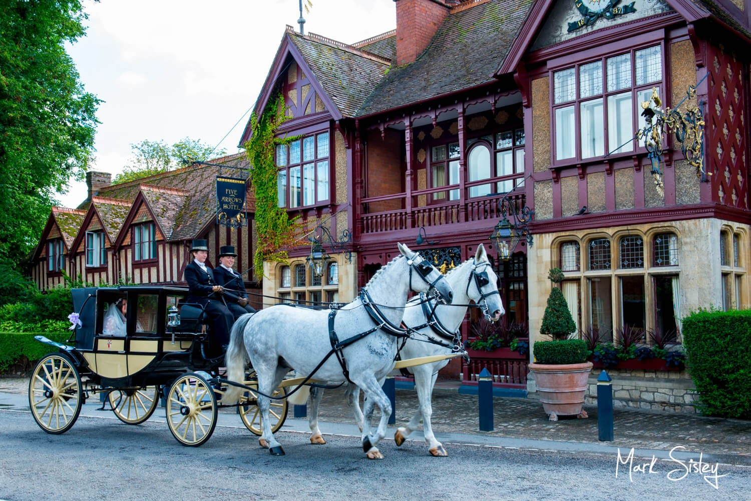 Dairy Waddesdon wedding photos of horses and carriage passing The Five Arrows Hotel in the village