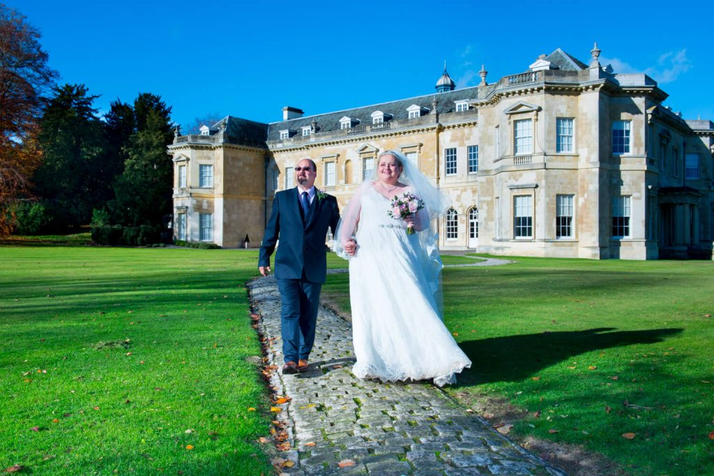 Hartwell House autumn wedding of the newlyweds walking along the cobbled footpath