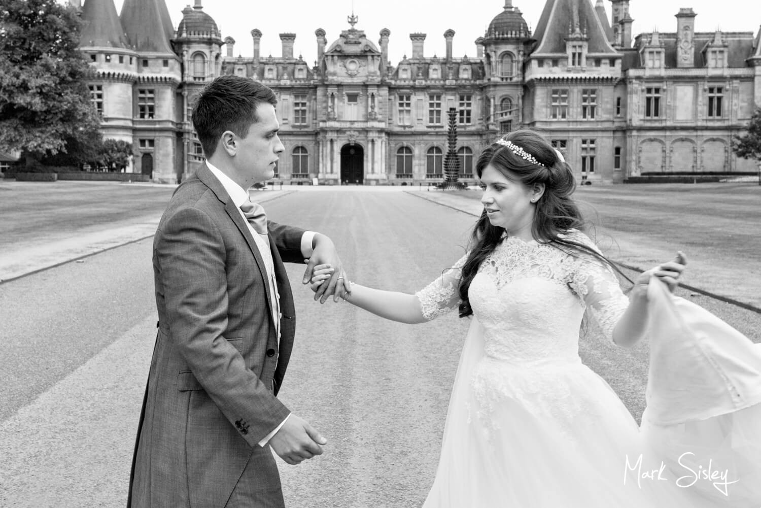 Bride and groom practicing their wedding first dance in front of Waddesdon Manor