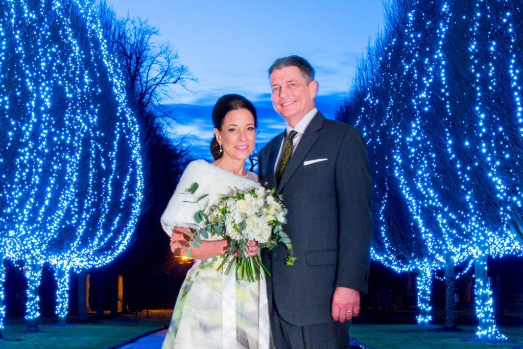 Danesfield House winter wedding photography of the newlyweds with the illuminated tree aisle at the entrance
