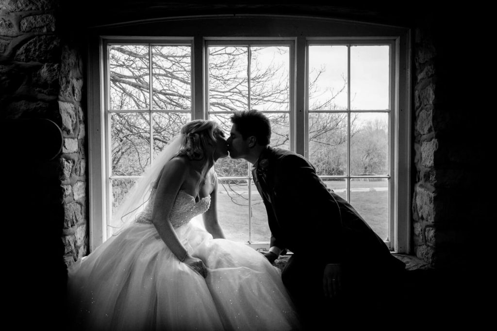 Notley Tythe Barn wedding photography - silhouette image of bride and groom kissing in the window