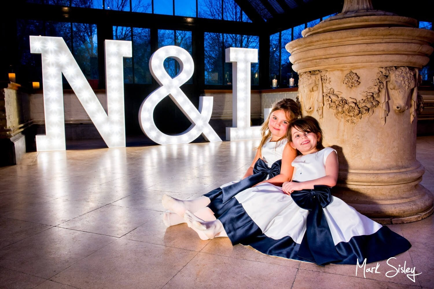 The Dairy Waddesdon Spring wedding shot of the flowergirls with giant illuminated letters