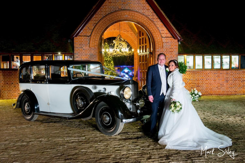 Waddesdon Dairy Christmas wedding pose with the newlyweds glitzy car