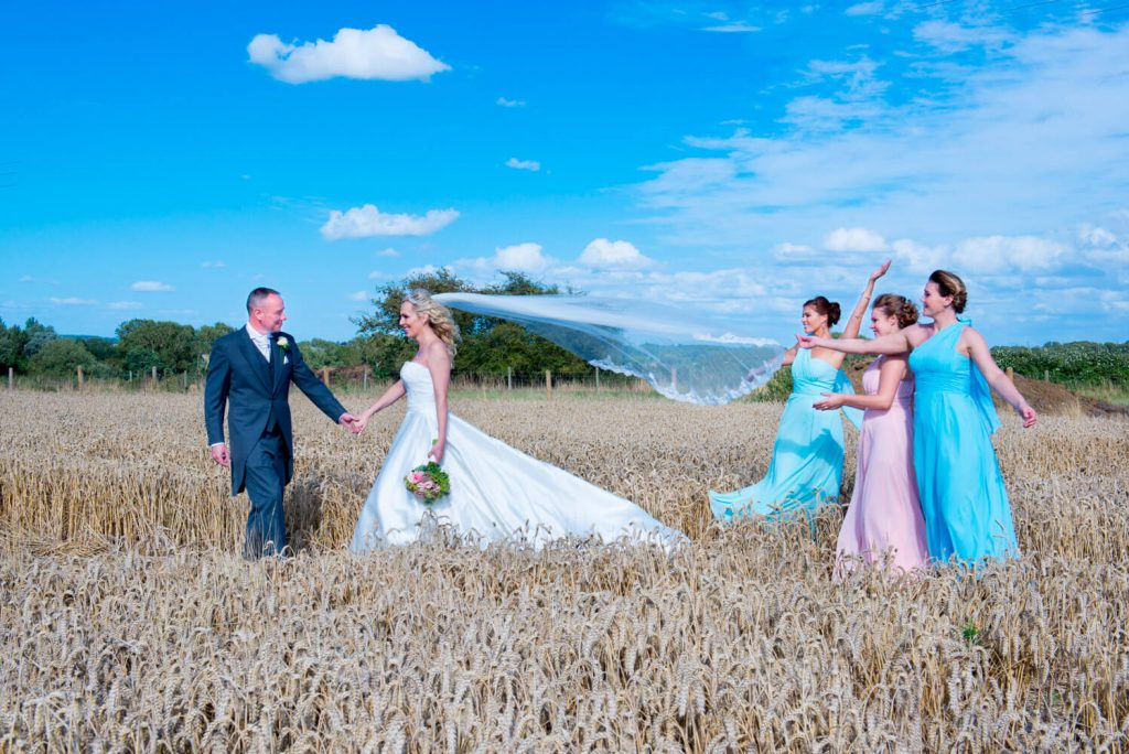 Notley Tythe Barn wedding photography - bride and groom and bridesmaids in a wheat field