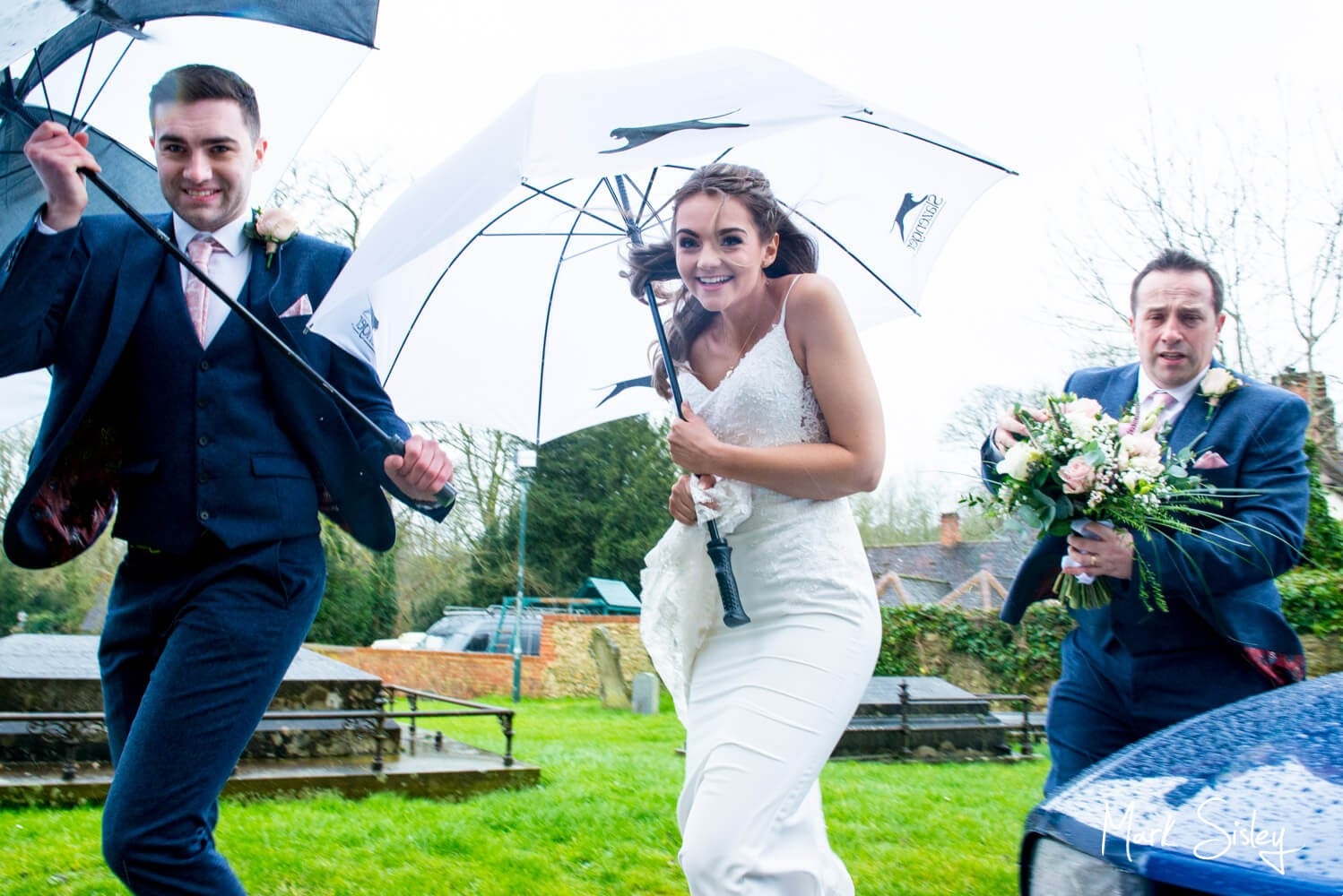 The bride arrives at the church for her Waddesdon Manor wedding during Storm Dennis
