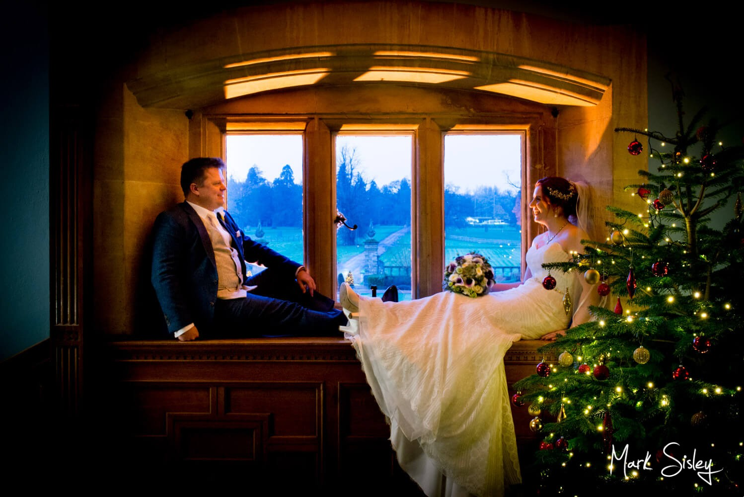Eynsham Hall winter wedding pose in the window by the Christmas tree