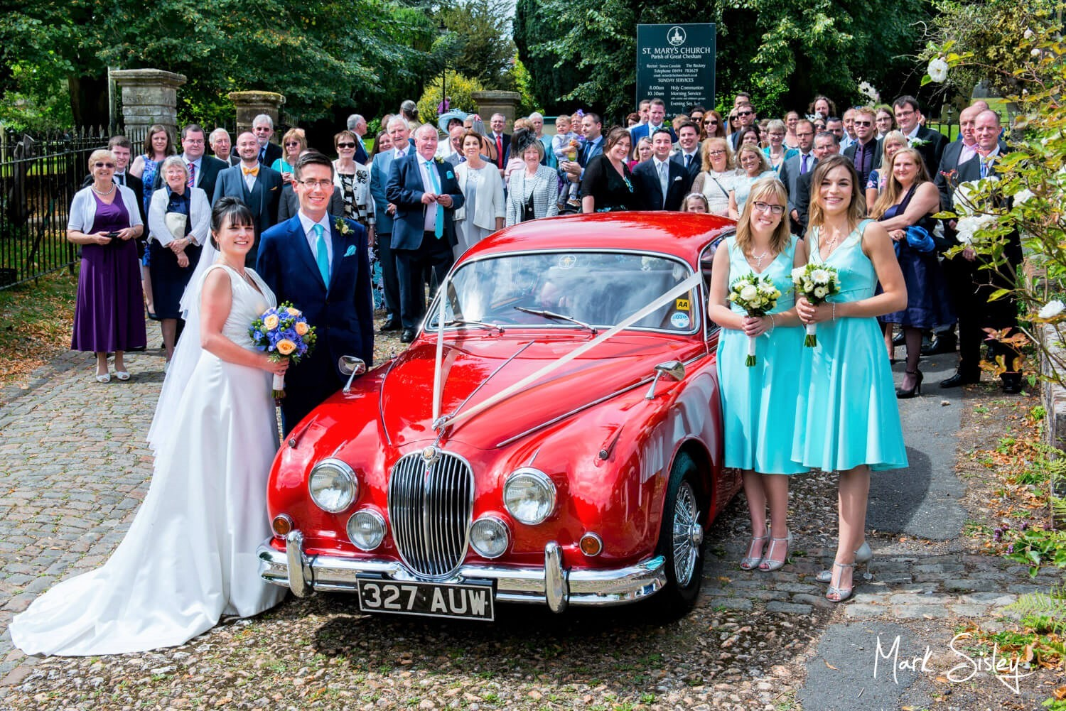 Bride and groom and wedding guests with red Jaguar at Chesham wedding