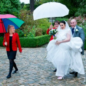 Hartwell House wedding photography of the bride arriving for the ceremony under rainy skies