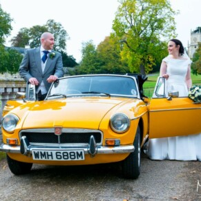 Hartwell House wedding photography of the bride and groom with their lovely vintage car