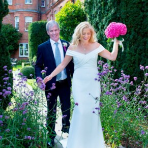 Grove Hotel Watford wedding photography of the newlyweds navigating through the flower borders